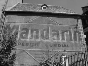"""Publicité pour l'apéritif """"Mandarin"""", photographié en 2009 sur un mur de l'enceinte médiévale d'une ville de Lozère. Source : http://archeologue.over-blog.com/article-36719304.html"""
